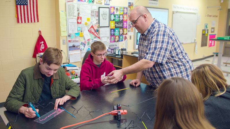 Teachers work with students to demonstrate how the 3Doodler pen works, with the pictured plastic pieces used to fill the device and form the basis for the 3D pen ink.