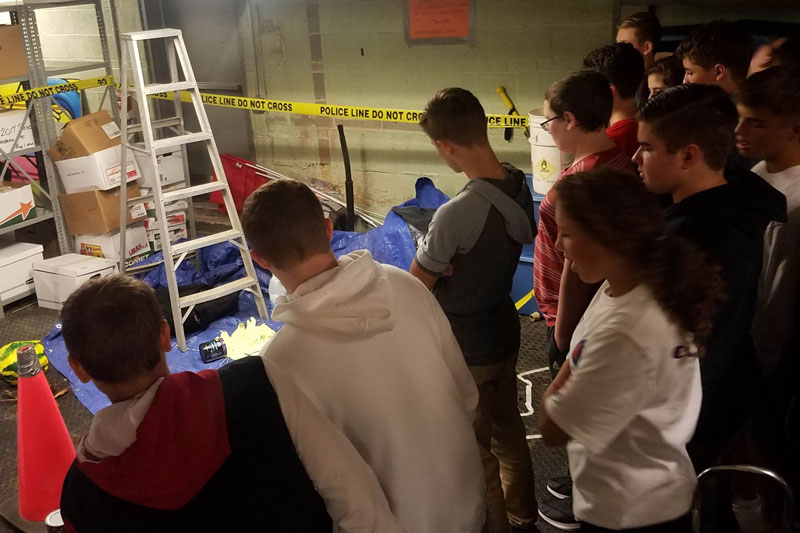Students in their 9th grade science class are surveying a mock crime scene in order to learn the skills of observation. This is the type of activity that can't be replicated through the distance learning environment.