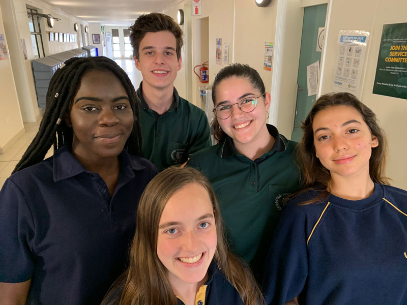 Social Media students pose for a picture in the high school hallway while venturing through the school for photos and content to post online.